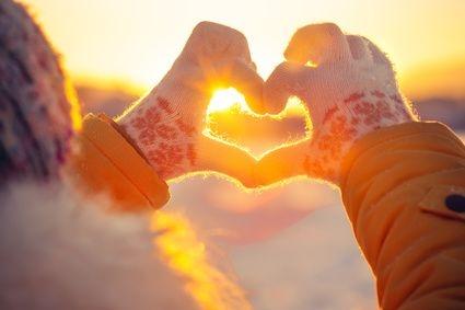 Hände in Strickhandschuhen formen ein Herz