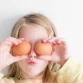 blondes Mädchen hält sich Eier vor die Augen und macht eine Grimasse